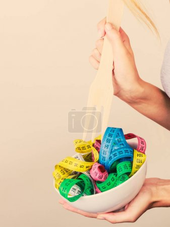 Diet. human hand and measuring tapes in bowl