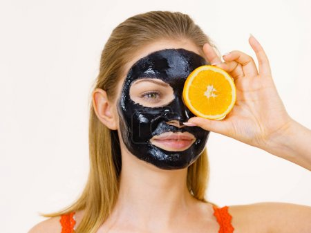 Photo pour Femme avec le masque noir de detox de detox de carbo de peel-off sur le visage retenant le fruit orange. Fille de l'adolescence prenant soin de la peau grasse, nettoyant les pores. Traitement de beauté. Soins. - image libre de droit