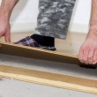 Man removing laminate of floor in house shoes...