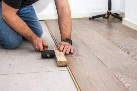 Man removing laminate on the floor in socks...