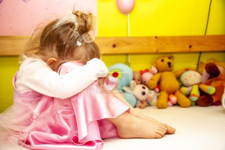 Photo for Cute little girl sitting on bed very unhappy. - Royalty Free Image