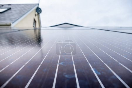 Foto de Paneles fotovoltaicos instalados en un rack junto a casa con paneles solares para agua caliente . - Imagen libre de derechos