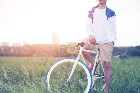 Photo pour Jeune homme en t-shirt blanc, assis sur son vélo dans le domaine (soleil intentionnelle éblouissement et vintage de couleurs) - image libre de droit