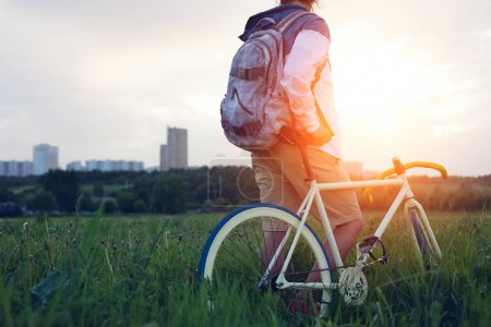 Young man with bicycle in the green field looking at sunset