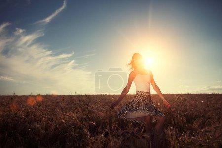 Photo pour Jeune et belle fille dansant dans le domaine du blé au coucher du soleil (éblouissement intentionnel du soleil et éruptions de lentilles ) - image libre de droit
