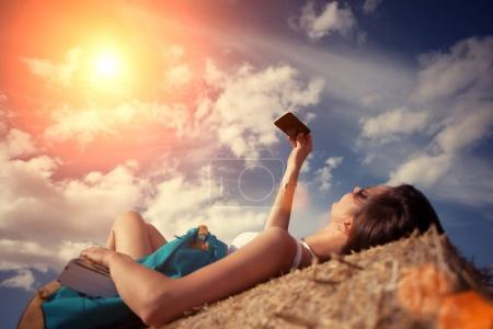 Girl lying on haystack with and mobile phone