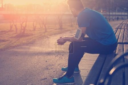 Photo pour Athlète masculin reposant sur un banc dans le parc au coucher du soleil après la course (éblouissement intentionnel du soleil et couleur vintage ) - image libre de droit