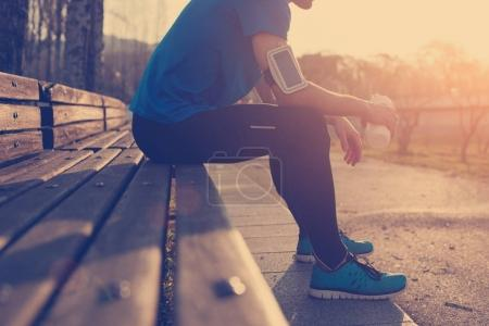 Athlete resting on bench in park at sunset after running with bo