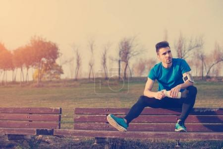 Handsome athlete resting on the bench in park with bottle of wat