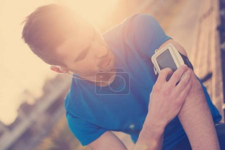 Athlete finding music on mobile phone on his arm (intentional su