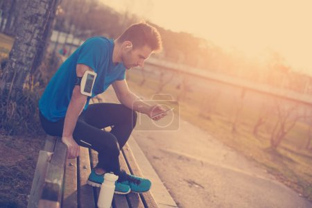 Male athlete sitting in the park at sunset with mobile phone, ar