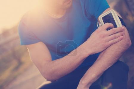 Athlete touching armband with mobile phone on his arm (intention
