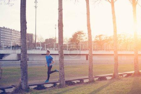 Athlete running in the park at sunset (little motion blur, inten