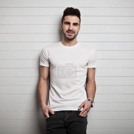 Photo pour Homme en t-shirt blanc, fond mural en bois - image libre de droit