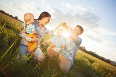 happy young family spending time in the park in sunny day