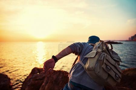 Photo pour Voyageur avec sac à dos près de la mer rampant au coucher du soleil - image libre de droit
