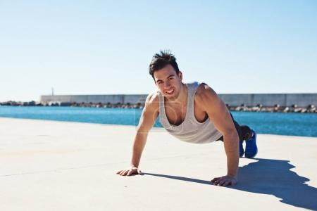 Smiling fit athlete doing push up outdoors