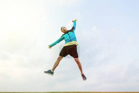 happy sportsman jumping with a bottle of water in hand