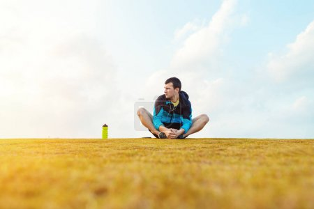 sportsman with a bottle of water sitting and doing warming stretching exercise in the park