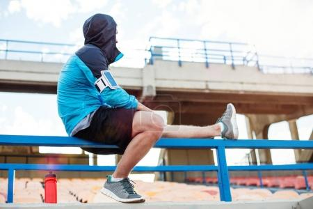 sportsman resting on the railing at stadium