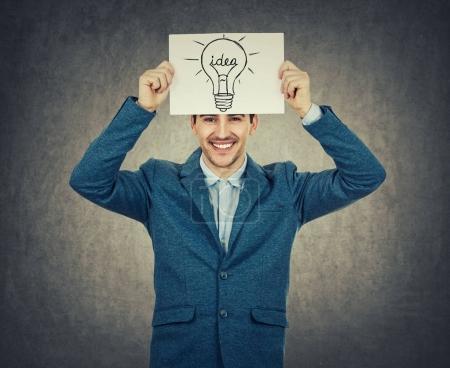 Photo pour Sourire d'homme d'affaires ou un enseignant tenant un livre blanc au-dessus de sa tête avec une esquisse de l'ampoule. Science et les affaires idée concept isolé sur fond gris. - image libre de droit