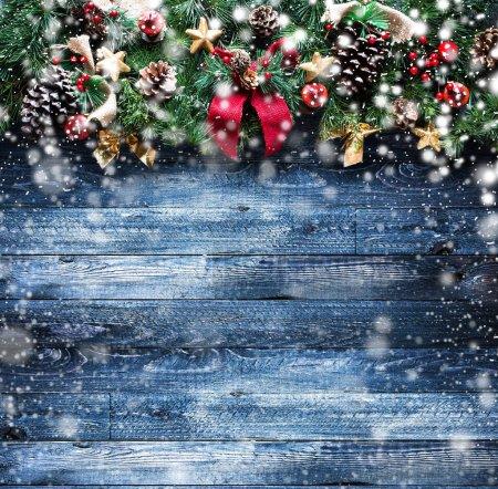 Photo pour Cadre de Noël joyeux avec neige et vrai bois pin vert, boules colorées, noeuds avec des baies et d'autres choses de saison sur un vieux fond en bois vieilli - image libre de droit