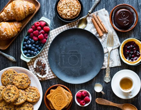 Top view of a wooden with  of cakes, fruits, coffee