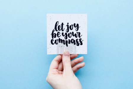 Photo for Minimal composition on a blue pastel background with girl's hand holding card with quote -  Let joy be your compass - Royalty Free Image