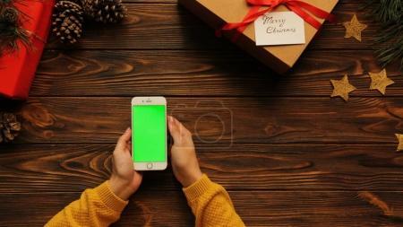 Photo pour Vue du dessus des mains de la femme faisant défiler son téléphone blanc sur la table en bois pendant Noël, écran vert, clé chromatique - image libre de droit