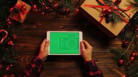 Photo pour Vue de dessus. Les mains féminines tapotant, faisant défiler et zoomant sur l'ordinateur tablette horizontalement. Le bureau en bois décoré avec des lumières de Noël. Écran vert, clé chromatique . - image libre de droit