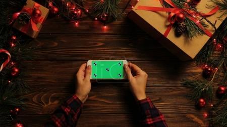 Photo pour Vue de dessus. Femme tapotant, faisant défiler et zoomant sur le téléphone mobile horizontalement. Le bureau en bois décoré avec des lumières de Noël. Écran vert, clé chromatique. Mouvement de suivi . - image libre de droit