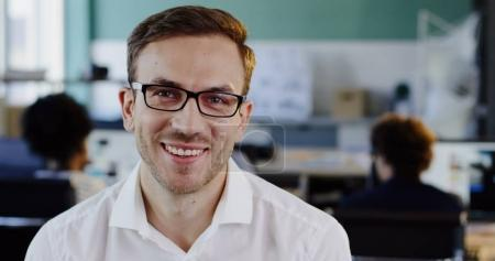 Close up of Caucasian handsome man in white shirt in glasses looking straight in the camera and smiling cheerfully. The blurred office background. Portrait. Indoors