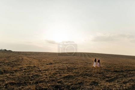 two girls walking in field