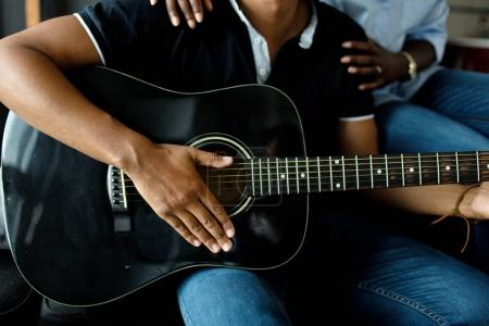 Photo for Male hands playing black acoustic guitar, female hands on man shoulders - Royalty Free Image
