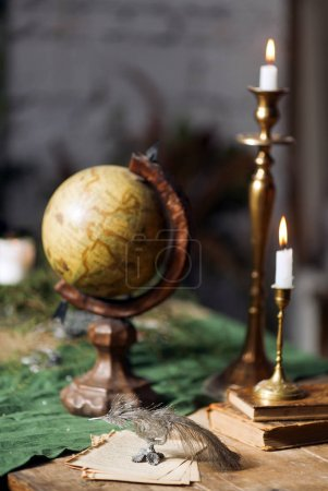 Globe, candelabre and candles, old books