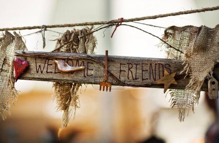 closeup daytime view of wooden sign with Welcome Friends words decorated with fabric and small objects