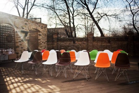 daytime view of colorful chairs arranged in rows in building yard