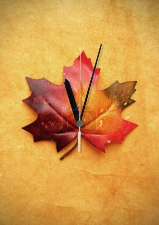 Photo for Autumn maple leaf with clock hand - Royalty Free Image