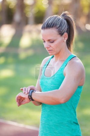 Fit female athlete looking at her watch