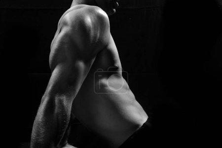 Photo pour Modèle de fitness masculin montrant les muscles en studio avec un fond noir - image libre de droit