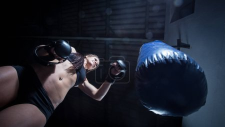 Female boxer punching a punching bag