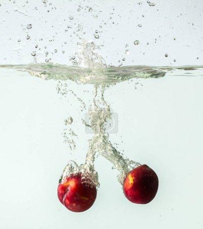 Peaches splashing into water