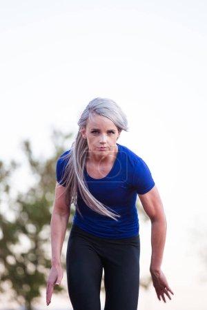 Female athlete sprinting on a tartan athletics track