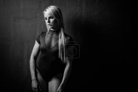 Photo pour Modèle de fitness féminin sexy dans un studio avec éclairage dramatique et tenue sexy - image libre de droit