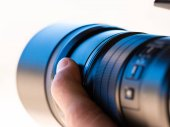 Close up of a camera telephoto lens being hand held by a photogr