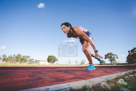 Photo pour Athlète modèle et piste femme fitness, Sprint sur une piste d'athlétisme en tartan - image libre de droit