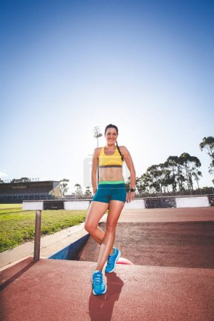 Female fitness model and track athlete  on an athletics track made from tartan