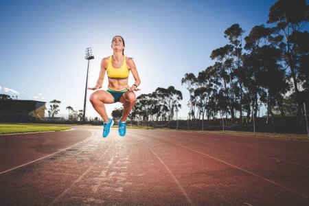 Photo for Female fitness model and track athlete  on an athletics track made from tartan - Royalty Free Image