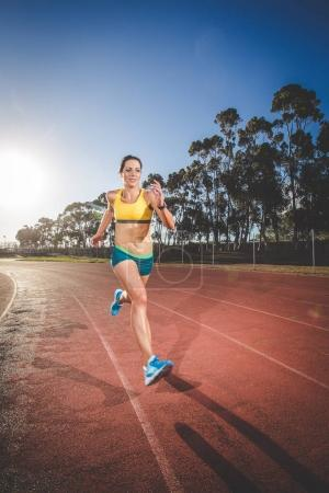 Photo for Female fitness model and track athlete sprinting on an athletics track made from tartan - Royalty Free Image