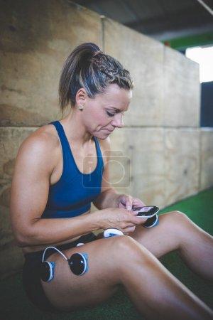 Photo pour Modèle de fitness féminin utilisant la technologie de stimulation musculaire électronique après une séance d'entraînement difficile . - image libre de droit